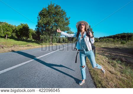 Young Attractive Woman Tourist With Backpack Hitchhiking On The Road. Traveling By Autostop. Backpac