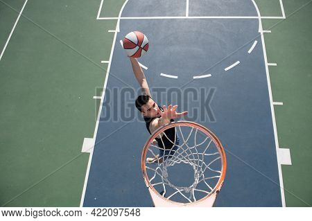 Basketball Concept. Man Jumping And Making A Slam Dunk Playing Streetball, Basketball. Urban Authent