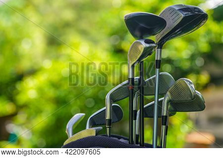 Golf Bag And Clubs In Front Of A Blurred Golf Course Background, Set Of Golf Clubs Over Green Field