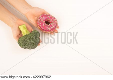 Comparison Of Eating Habits. Woman Holding Broccoli And Donut On A White Background. Copy Space