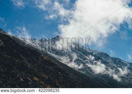 Atmospheric Mountain Landscape With High Black Rock Peak With Snow In Low Clouds. Beautiful Alpine S