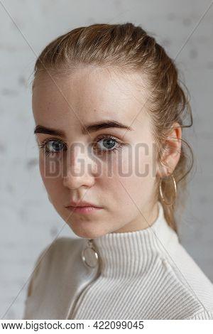 Closeup Portrait Of Cute Thoughtful Teen Model Wearing White Sweater. Caucasian Skinny Young Female