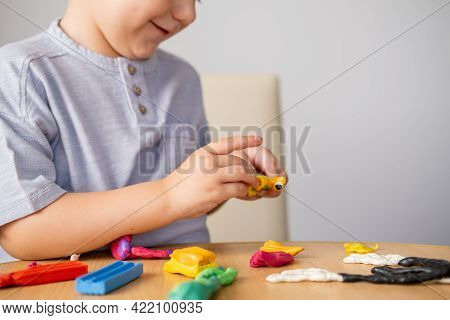 Happy Little Boy Sculpts From Plasticine While Sitting At The Table.