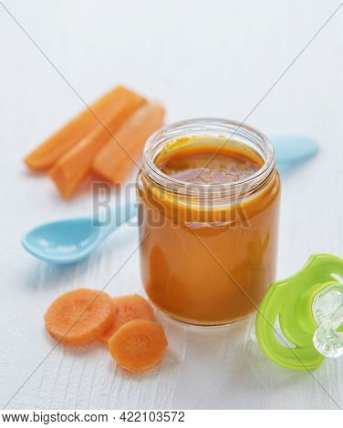 Baby Carrot Mashed With Spoon In Glass Jar
