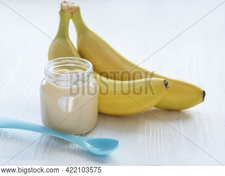 Jar Of Banana Puree And Bananas On Wooden Table