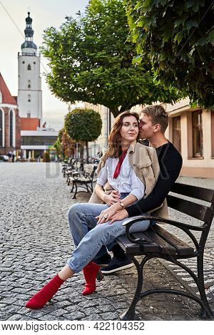 Beautiful Young Couple Cuddling On A Bench In A European Town. Romatnic Date And Love Concept.