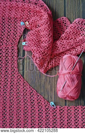Crocheting With Pink Cotton Threads On A Dark Wooden Background.