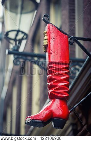 Amsterdam - 9th July 2014: The iconic wooden red boot outside of the De Roode Laars, meaning Red Boot Bar, Amsterdam. The boot is a symbol that the building once housed a local shoe and bootmaker.