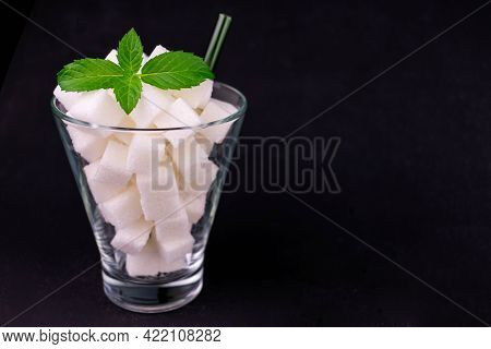 A Glass Full Of Sugar On A Black Background. The Concept Of Harmful Sweet Carbonated Drinks.
