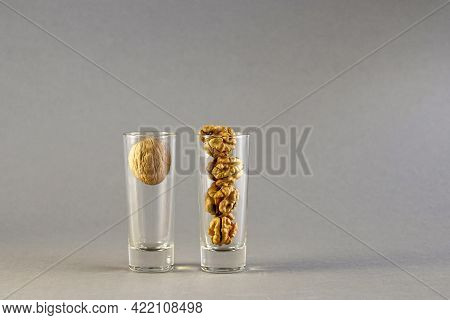 Walnut And Walnut Kernels Are Placed In Two Glass Cylindrical Glasses On A Gray Background. Close-up
