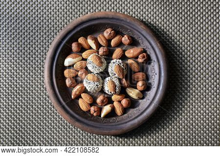 Various Nuts Are Laid Out In A Brown Handmade Clay Plate. Almonds, Hazelnuts, Brazil Nuts And Sweets