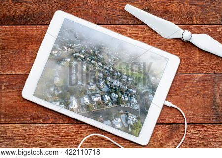 foggy spring morning over residential area of Fort Collins in northern Colorado after heavy rain and snow, reviewing aerial image on a digital tablet