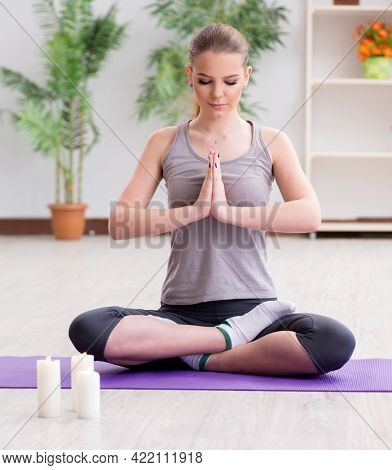 Young woman in lotus pose meditating in spa gym