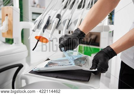 Close Up Of Dentist Hands In Black Sterile Gloves Opening Package With Sterile Dental Instruments. D