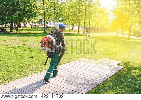 Park Worker Removes Dry Leaves And Bullets With An Industrial Vacuum Cleaner. Men Work Outdoors In T