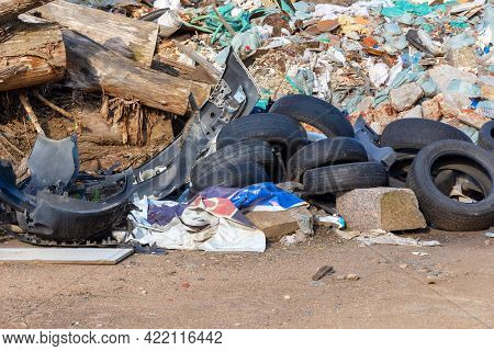 Illegal Dump Of Construction Waste And Old Car Tires. The Concept Of Damage And Harm To The Environm
