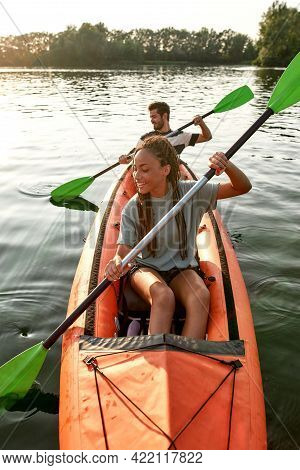 Adventurous Young Girlfriend Paddling Kayak On A River Together With Her Boyfriend On A Summer After