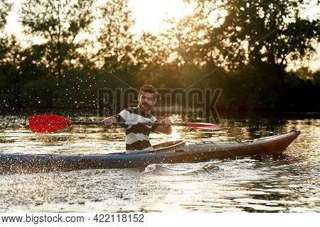Active Young Caucasian Guy Looking Cheerful While Paddling Kayak On A Lake Surrounded By Nature. Kay