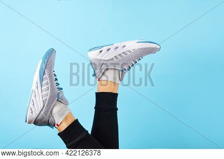 Male Legs Wearing Sneakers Over Blue Background. Sport Shoes For Training In The Gym. Man In Running
