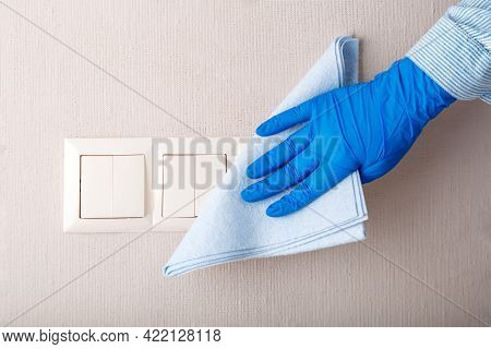 Light Switch Surfaces Disinfection. Woman In Rubber Blue Glove Clean Light Switch With Cloth On Wall