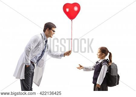 Doctor cardiologist giving a heart balloon to a schoolgirl isolated on white background