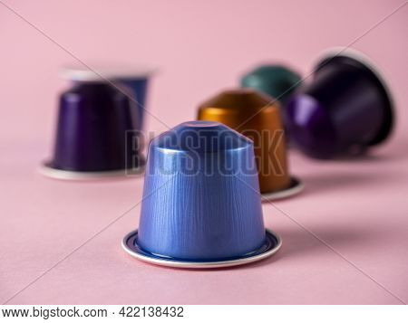 Colorful Aluminum Capsules With Ground Coffee On A Paper Rose Background. Capsules For The Coffee Ma