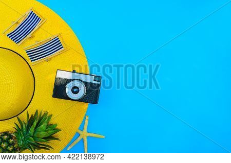 Yellow Hat With Camera And Pineapple On Blue Background For Summer Holiday.