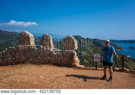 Kalekoy, Turkey - 20 October, 2019: Male tourist posing for photo on top of Simena castle ancient fortress at Mediterranean sea coast, Popular tourist destination
