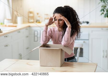 Wrong Item. Frustrated Young Woman Looking At Open Parcel With Despair