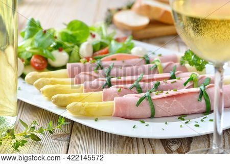 Delicious Spring Salad With Asparagus Rolled In Cooked Ham On A White Platter, Served With A Young D