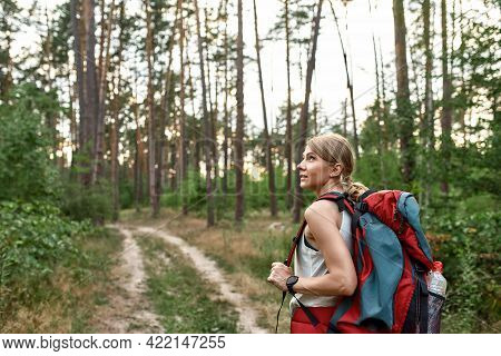 Young Caucasian Woman With Tourist Backpack Walking Alone In Green Wood And Looking To Side. Hiking,