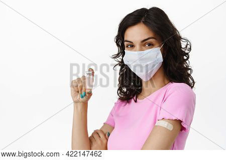 Covid-19 And Vaccination Concept. Brunette Israili Girl In Medical Mask Shows Ampule With Vaccine Fr