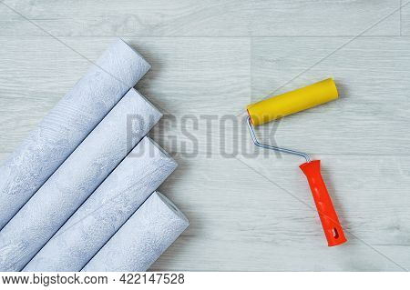 Gray Textured Wallpaper Rolls And Wallpaper Roller On A White Wooden Background.