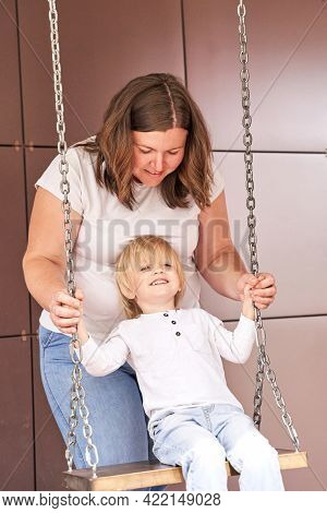Mother Push Little Son On Swing. Outdoor Family Portrait. Two Person Together. Happy Positive Feelin