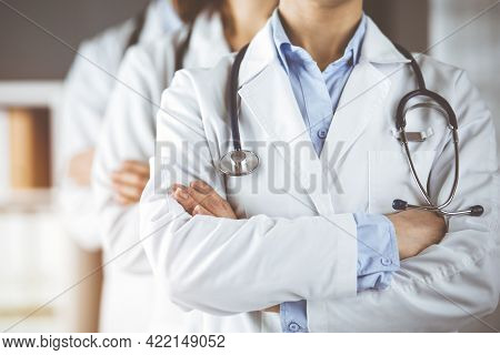 Group Of Modern Doctors Standing As A Team With Arms Crossed In Sunny Hospital And Ready To Help Pat