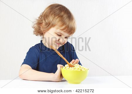 Little cute blonde boy refuses to eat cereal