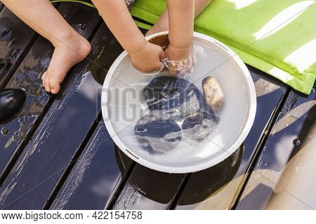 Close Up View Of Child Plays With Water In The Courtyard Of A Private House. Summer Weather Concept.
