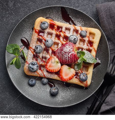 Delicious waffles with berries, mint, powdered sugar and sweet sauce on ceramic black plate on grey background. Top view. Sweet meal. Dessert. Serving food