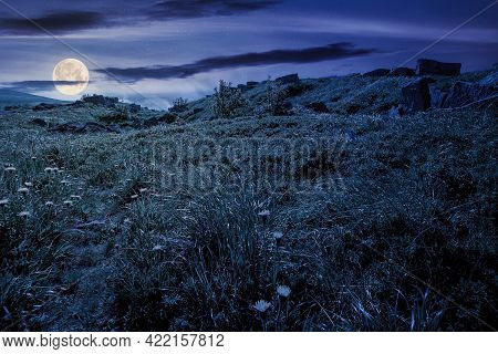 Mountain Meadow At Night. Cloud Rolling Above The Hill With Rocks Among The Grass In Full Moon Light