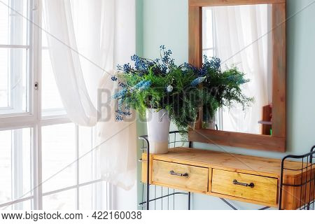 Elegant Mirror In Wooden Frame Above Fancy Console Table With Flowers In Vase In Trendy Rustic Bedro