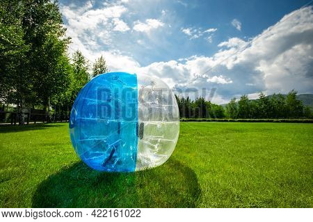 Zorbing Balloon On The Summer Lawn. Inflatable Zorb Ball Outdoor. Leisure Activity Concept With Copy