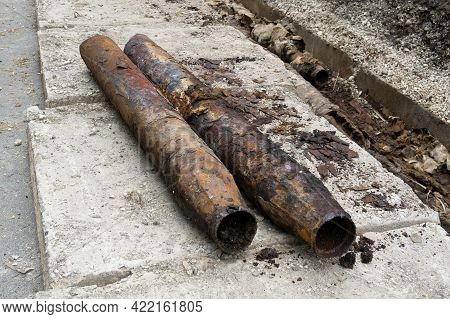 Fragments Of Old Cast-iron Water Pipes. Rusty Steel Tube With Holes Of Metallic Corrosion. Dismantli