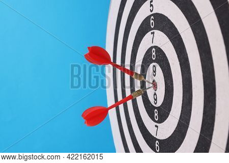 Game Darts In Center With Darts On Blue Background.