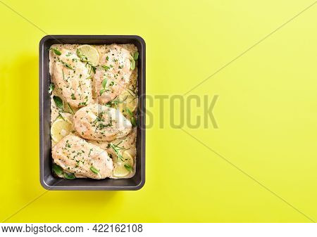 Chicken Breast In Creamy Garlic Sauce In Baking Dish Over Yellow Background With Free Text Space. He