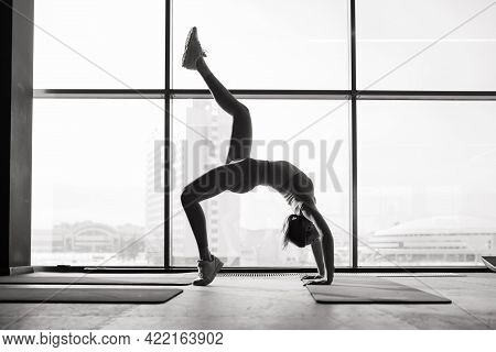 Woman Practicing Advanced Yoga On Mat Against Large Window