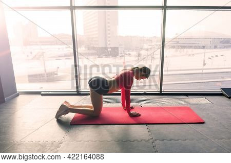 Woman Practicing Advanced Yoga On Mat Against A Large Window