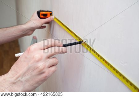 Man Repair Measures The White Wall Of The With A Tape Measure And Before Wallpapering. Renovation Ap
