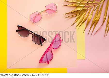 Stylish Pink Sunglasses On Color Summer Background With Gold Palm Leaves. Fashionable Trendy Optics
