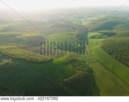 Aerial View Of Green Summer Forest With Green Fields At Majestic Sunrise, Meadows. Drone Flying Spri