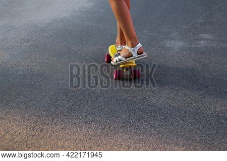 Defocus Skater Moving Along Asphalt Road On A Yellow Skateboard Wearing White Sandals. Some Of The L